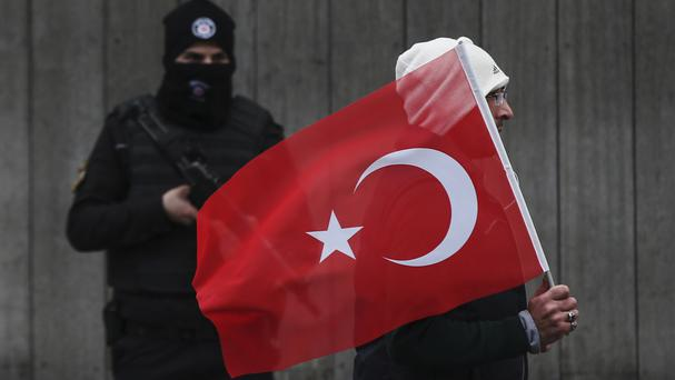 A man with a Turkish flag walks past a police officer during a memorial outside the Reina club following the New Year's Day attack in Istanbul (AP/Emrah Gurel)