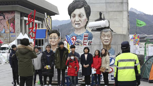 People pose for photos in front of effigies of impeached South Korean president Park Geun-hye and others (Ahn Young-joon/AP)