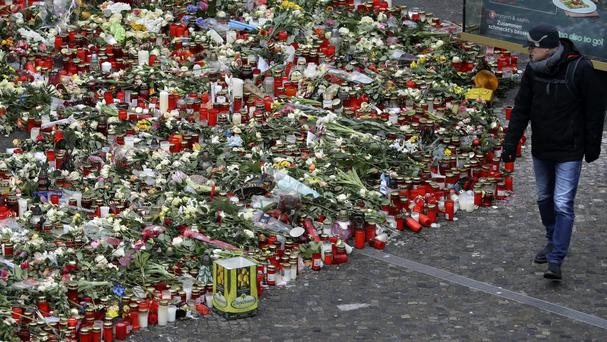 A man walks past flowers close to the Christmas market at Breitscheid square in Berlin (Michael Sohn/AP)