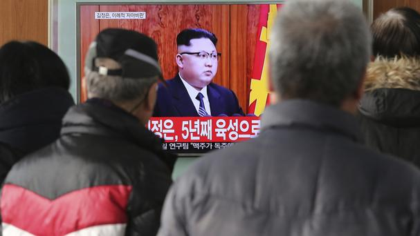 South Koreans watch a TV news programme showing North Korean leader Kim Jong Un's New Year speech (Ahn Young-joon/AP)