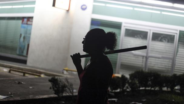 A woman holds a stick as she and her neighbours try to prevent looting in the port city of Veracruz (AP/Felix Marquez)