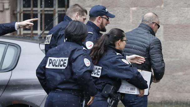 Former Kosovo prime minister Ramush Haradinaj, right, is rushed by police into Colmar courthouse (AP)