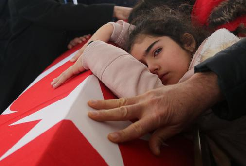 Nisa, eight-year old daughter of police officer Fethi Sekin, who was killed in an attack on Izmir courthouse on Thursday, mourns over her father's coffin during a funeral ceremony in Izmir, Turkey, yesterday. Photo: Reuters/Hakan Akgun