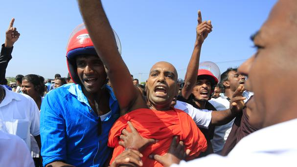 A Sri Lankan Buddhist monk and villagers shout slogans during the protest (AP)