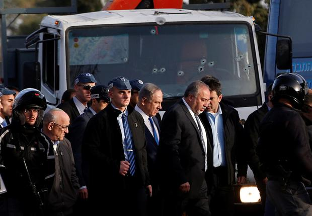 Israeli prime minister Benjamin Netanyahu, centre, and defence minister Avigdor Lieberman visit the scene of the attack in Jerusalem yesterday. Photo: Reuters/Ronen Zvulun
