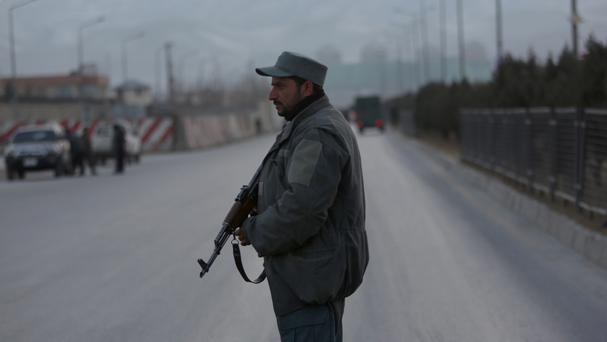 A member of the Afghan security forces stands guard near the site of the blasts in Kabul (AP/Rahmat Gul)