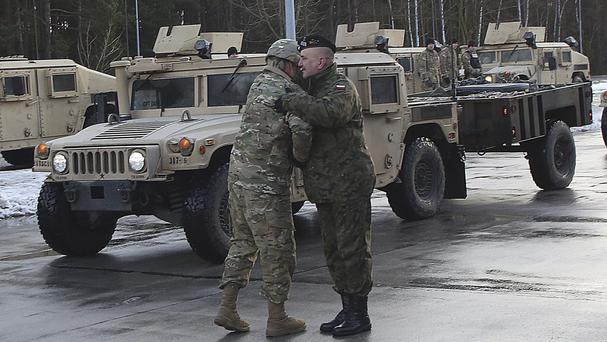 A US soldier is welcomed by a Polish army official as US army vehicles cross the Polish border in Olszyna (Czarek Sokolowski/AP)