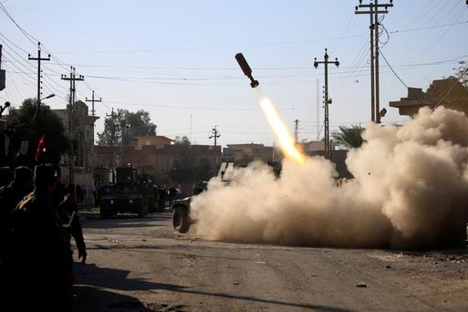 Members of the Iraqi rapid response forces fire a missile toward Isil militants in eastern Mosul. Photo: Reuters