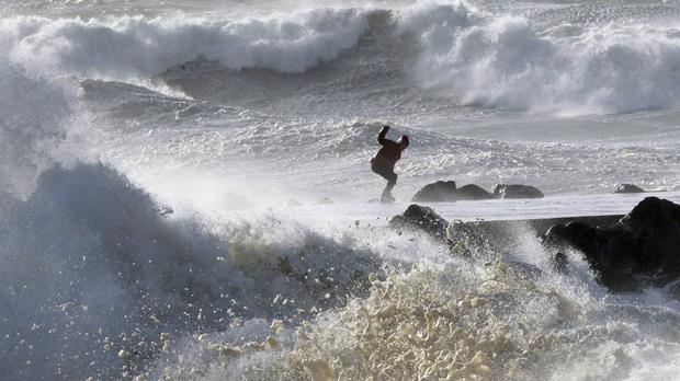 A man tries to keep his balance as waves hit the seawall at the beach in Anglet, south-western France (Bob Edme/AP)