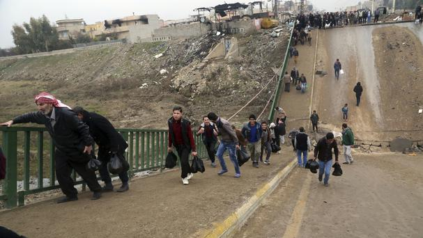 People cross a bridge destroyed by Islamic State militants in a neighbourhood recently liberated on the eastern side of Mosul (AP/Khalid Mohammed)