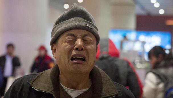 Wen Wanchang, whose son was on board the missing Malaysia Airlines Flight 370, reacts as he arrives at a train station in Beijing (AP)