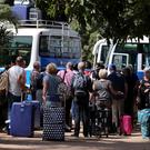 Tourists board buses leaving for the airport in Bajul yesterday Pictures: Reuters