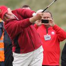 Donald Trump hits the first tee shot on the first hole of the Trump International Golf Links golf course near Aberdeen after officially opening it