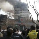 People watch the Plasco building where smoke rises from its windows in central Tehran, Iran (AP)