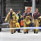 Rescue workers at the scene after a car struck pedestrians in the central business district of Melbourne (AP Photo/Andrew Brownbill)