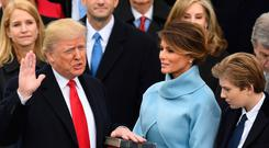 Donald Trump takes the oath of office as his wife Melania holds the bible and his son Barron looks on. Photo: Getty