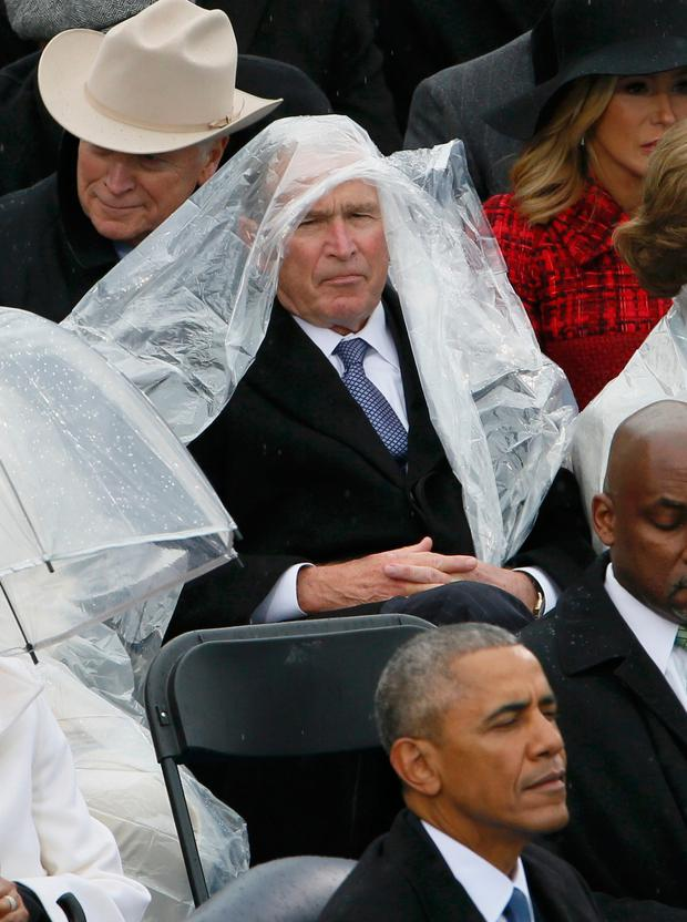 Former President George W. Bush keeps covered under the rain. Photo: Reuters
