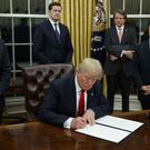 President Donald Trump, flanked by senior colleagues, signs his first executive order on healthcare in the Oval Office (AP Photo/Evan Vucci)