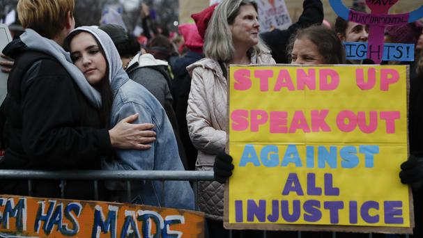 Protesters wait for speakers along the barricades at the Women's March on Washington (AP)