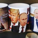 Cups depicting Vladimir Putin and Donald Trump displayed for sale in St Petersburg, Russia (AP)