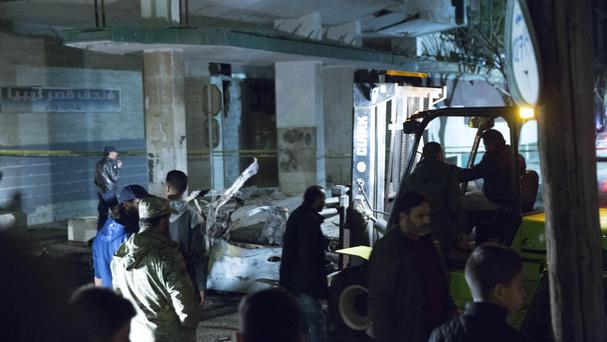 Security officers gather at the site of a car bombing near the Italian embassy in Tripoli (AP/Mohamed Ben Khalifa)