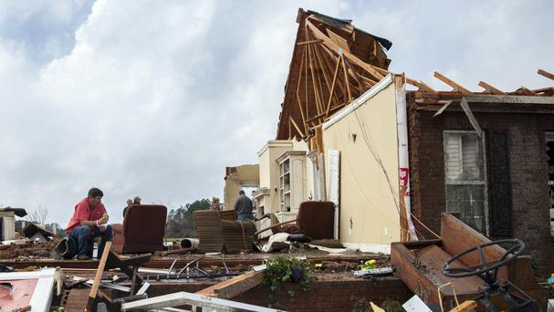 A man sits in what used to be his home after violent storms hit southern US states (AP Photo/Branden Camp)