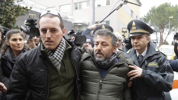 Alessio Feniello, the father of one of the 23 people still missing at the Hotel Rigopiano, is escorted by police officers as he is mobbed by journalists outside Pescara hospital (AP)