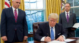 US President Donald Trump signs an executive order on US withdrawal from the Trans-Pacific Partnership while flanked by vice-president Mike Pence, left, and White House Chief of Staff Reince Priebus in the Oval Office of the White House in Washington. Photo: Kevin Lamarque/Reuters