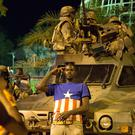 Gambians pose in front of military vehicles as Ecowas troops from Senegal secure the area near the State House in the capital Banjul (AP/Jerome Delay)