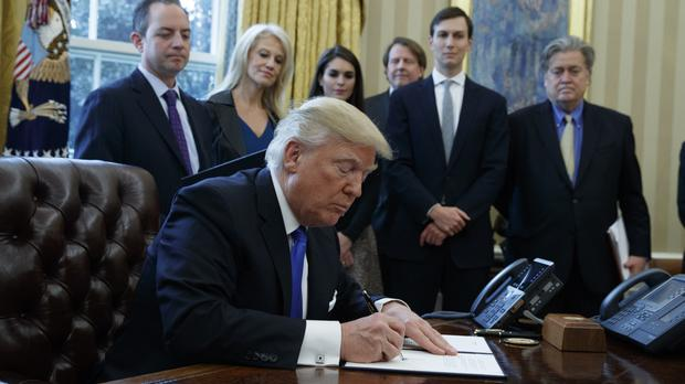 Donald Trump signs an executive order in the Oval Office of the White House (AP)