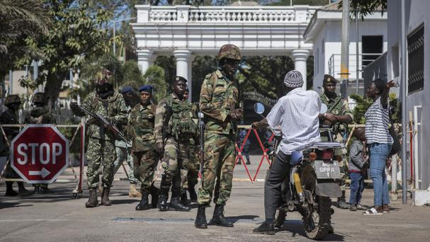 Senegalese soldiers check a motorcyclist at the entrance of the State House compound in Banjul, Gambia (Sylvain Cherkaoui/AP)