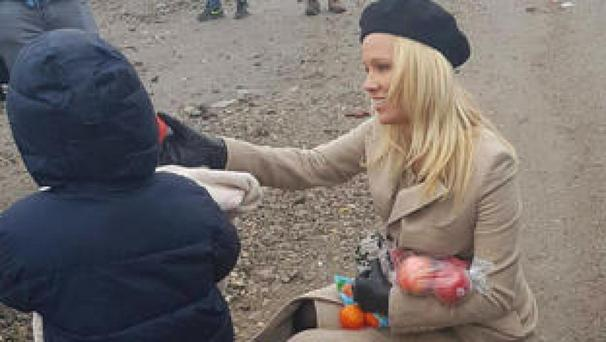 In this handout picture provided by PETA, actress Pamela Anderson delivers presents to children in the Grande-Synthe refugee camp in northern France (AP)