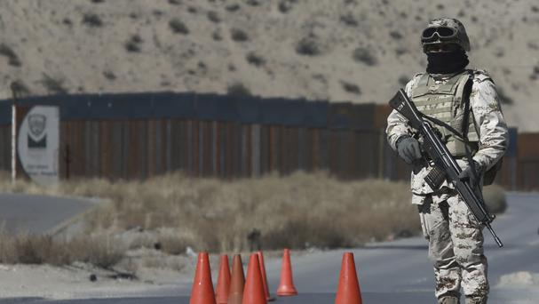 A Mexican soldier stands guard at a checkpoint near the Mexico-US border fence, on the Mexican side (AP)
