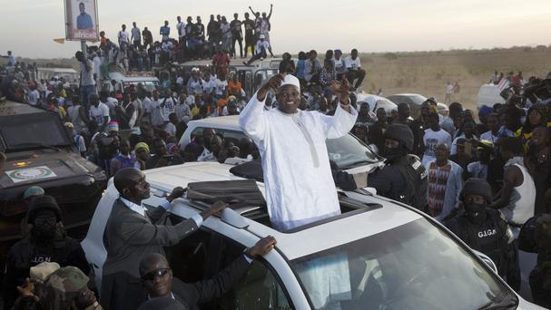 Gambian president Adama Barrow waves as he rides his motorcade through crowds of hundreds of thousands after arriving at Banjul airport in Gambia (Jerome Delay/AP)