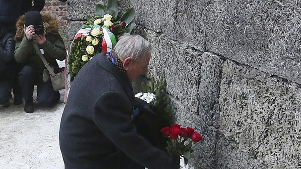 A holocaust survivor places flowers in commemoration of the people killed by the Nazis at the former Auschwitz Germany Nazi death camp in Oswiecim (AP)