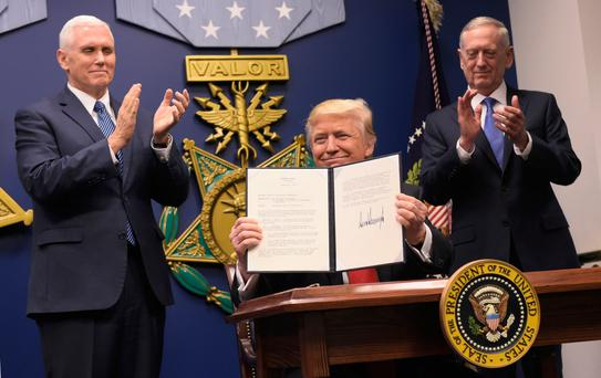 WITH A STROKE OF A PEN: US President Donald Trump holds up an executive action on rebuilding the armed forces at the Pentagon this weekend as US Vice President Mike Pence (L) and US Defense Secretary James Mattis applaud. Photo: Mandel Ngan/Getty