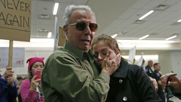 Iranian green card holder Shima Behgooy cries on the shoulder of her father-in-law Ahmad Behgooy, who is a naturalised US citizen, after being held at Dallas Fort Worth International Airport (Dallas Morning News/AP)
