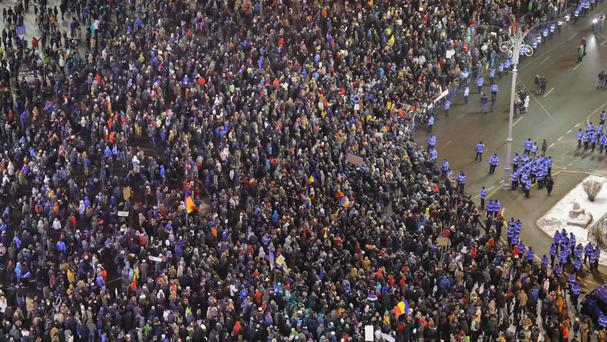 Protesters shout slogans outside government headquarters in Bucharest on Sunday (AP)
