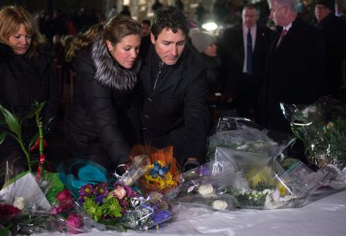 Canadian Prime Minister Justin Trudeau and his wife Sophie Gregoire Trudeau place flowers at a makeshift memorial during a vigil in Quebec City. Alexandre Bissonnette is escorted after appearing in court. Photos: The Canadian Press via AP