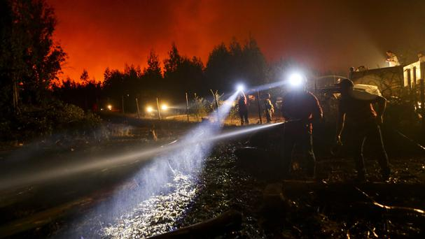A man waters the ground surrounding his home, threatened by a nearby wildfire in Portezuelo, Chile (AP Photo/Esteban Felix)