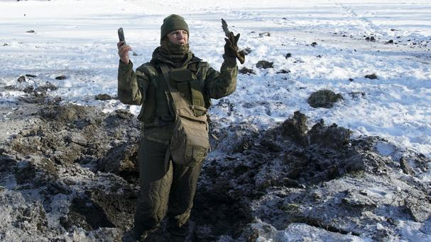 A Ukrainian soldier shows pieces of shrapnel in a crater left by an explosion in Avdiivka (AP Photo/Inna Varenytsia)