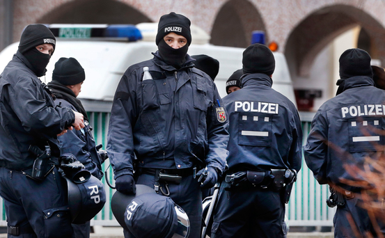 German police officers stand guard in front of a mosque during a terror raid in Frankfurt yesterday Photo: Michael Probst/AP
