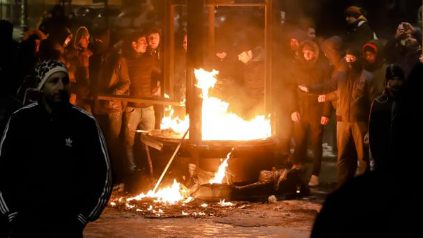People next to a burning kiosk after minor clashes erupted during a protest in Bucharest (AP Photo/Vadim Ghirda)