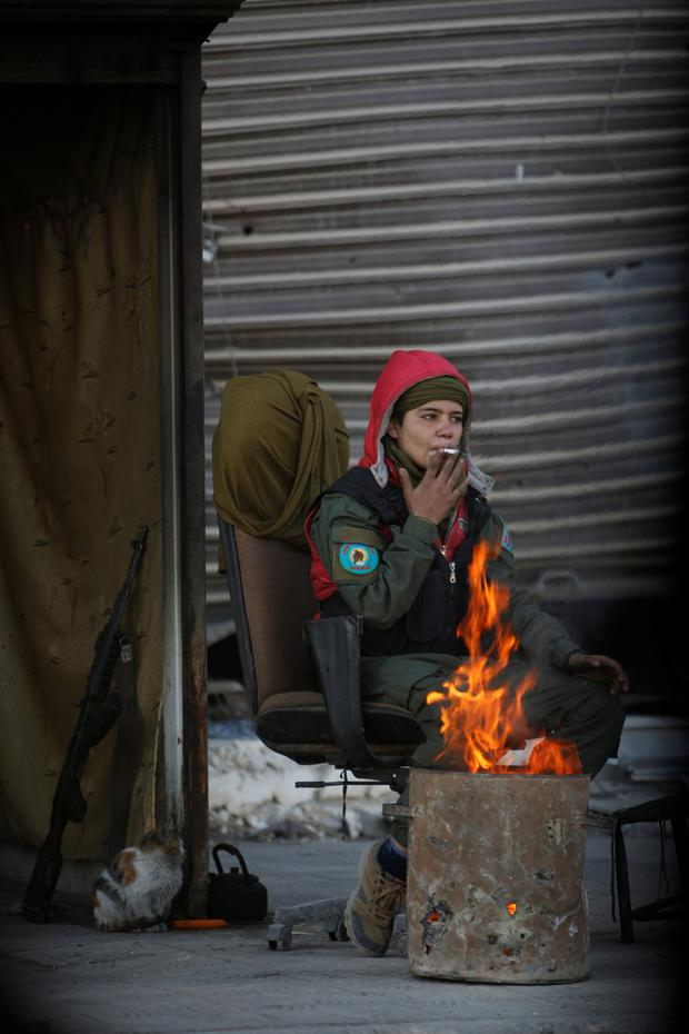 A Kurdish female fighter smokes a cigarette as she sits at the entrance of Bustan al-Basha area in Aleppo, Syria. Photo: Reuters