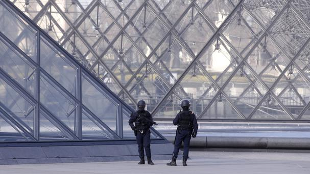Police officers patrol at the pyramid outside the Louvre in Paris (AP/Thibault Camus)