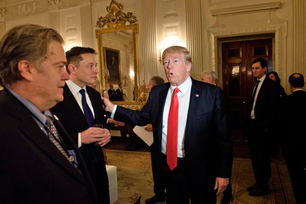 Adviser Steve Bannon, left, watches as President Trump greets Elon Musk, SpaceX and Tesla CEO, before a policy forum at the White House yesterday. Photo: Getty Images