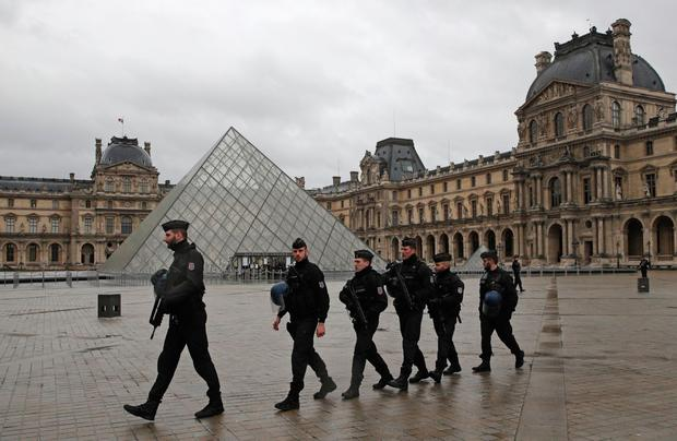 Armed police officers patrol in the courtyard of the Louvre museum near where a soldier opened fire after he was attacked in Paris. Photo: AP