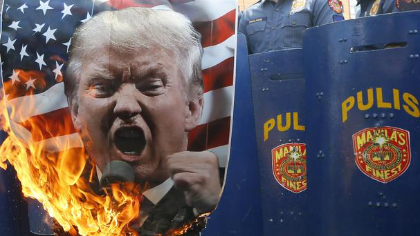 Protesters burn a portrait of Donald Trump during a rally at the US embassy in Manila (AP Photo/Bullit Marquez)