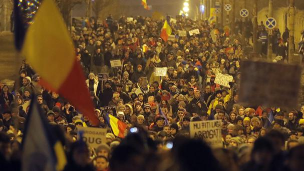 Demonstrators march in front of the government building during a protest in Bucharest (AP)