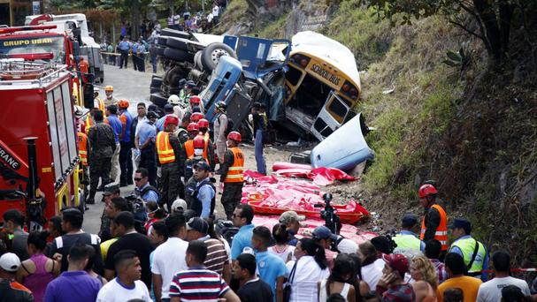 Emergency personnel respond to an accident involving a cargo truck and a bus on the outskirts of Tegucigalpa, Honduras (AP Photo/Fernando Antonio)